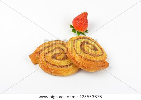 sweet cinnamon rolls and strawberry on white background