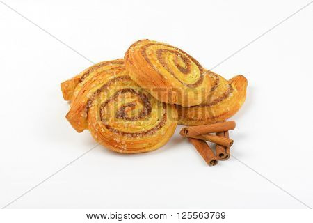 sweet cinnamon rolls and cinnamon sticks on white background
