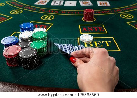 poker player holds cards. first-person view. female hand lifts the cards to see