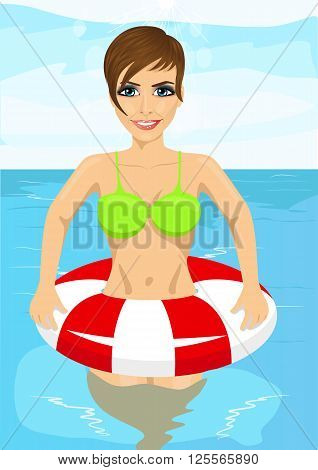 beautiful young woman standing in water with inflatable rubber ring