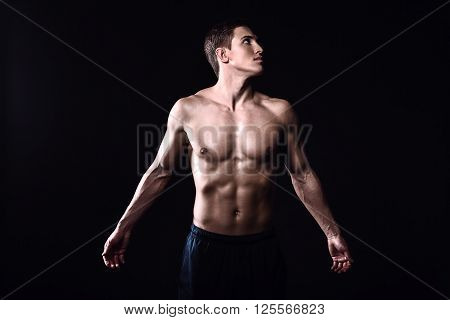 Attractive and muscular athlete. Studio shot of young shirtless sportsman on black background. Man with outstretched arms