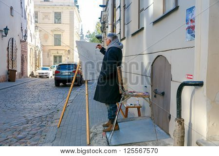 Riga, Latvia - 15 October, 2015: An old artist paints a building on the old street in Riga. The ancient architecture of the city attracts many artists.