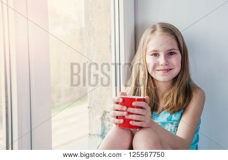 Little beauty girl sitting twith cup at the window