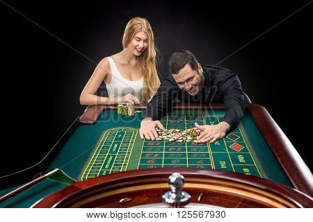 Couple playing roulette wins at the casino, gambling chips taken by hands man