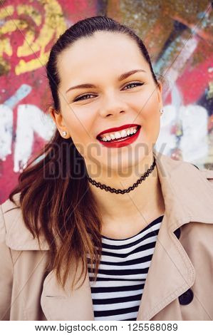 Portrait of a smiling emotional girl on a bright background. Cheerful mood concept vertical framing.