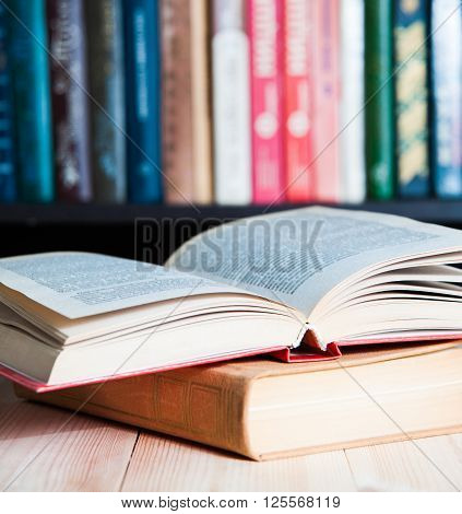 Open book on table  bookshelves background close up