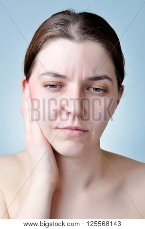 A young woman touching her inflamed ear