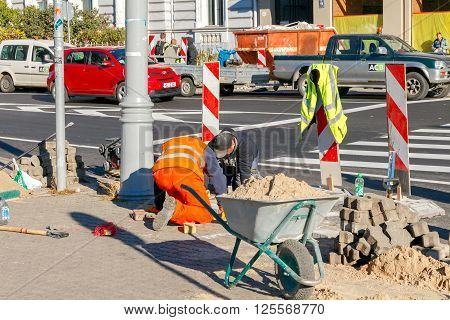 Riga, Latvia - 15 October, 2015: Masons workers make the pavement of stone blocks in the center of Riga.
