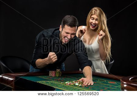 Young couple celebrating win at roulette table in casino,  gambling chips taken by mans hand. Addiction to  gambling