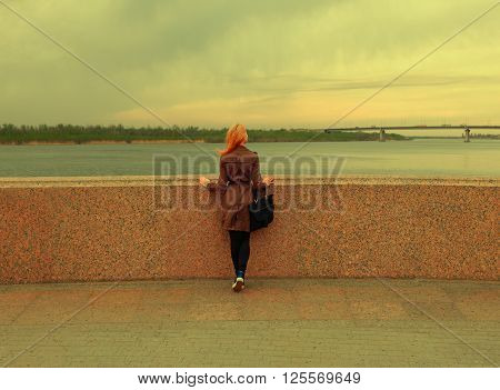 Beautiful young woman is looking at view over the river rear shot. Attractive girl enjoys summer and warm sunlight. The wind blew her hair. Vintage color, copyspace