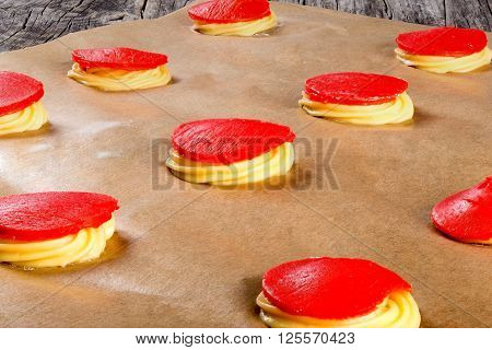 dough with red strawberry crumble for baking cakes shu eclairs on a parchment paper classic french recipe close-up
