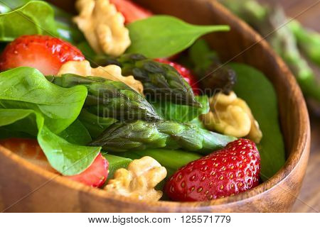 Fresh strawberry green asparagus baby spinach and walnut salad served in wooden bowl photographed with natural light (Selective Focus Focus on the asparagus head in the middle of the bowl)
