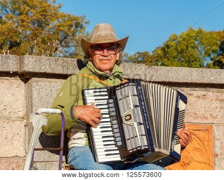 Riga, Latvia - 15 October, 2015: Old man in a hat entertains tourists playing the accordion at the Independence Square in Riga. Street musicians One of the attractions of the Latvian capital.