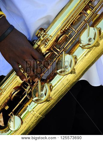African american male jazz musician performing on baritone saxophone outdoors.
