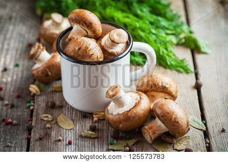 Mushrooms In White Enameled Mug, Dill And Spices On Wooden Table.