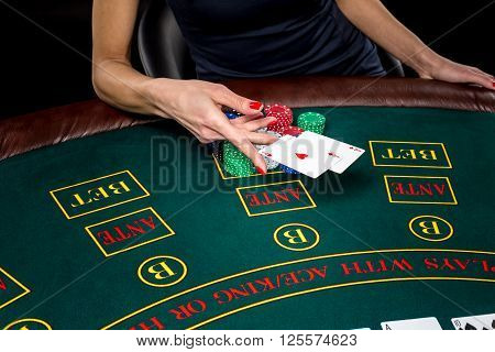 Poker play. Chips and cards on the green table. Cards in a player's hand. female hand throwing two aces. win