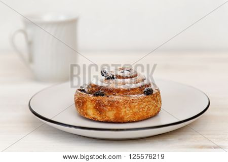 Cinnamon roll with raisins in a ceramic saucer and cup on blurred background. Shallow focus.
