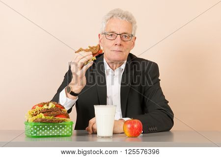 Senior business man eating his bread meal at the office