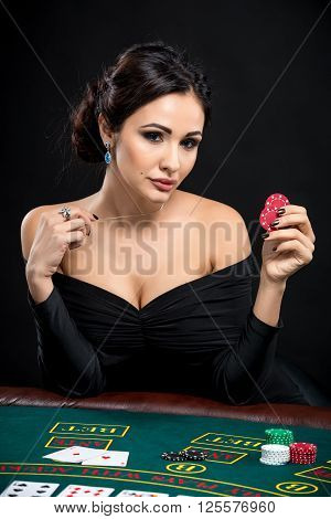sexy woman with poker cards and chips. Female player in a beautiful black dress. holding red chips