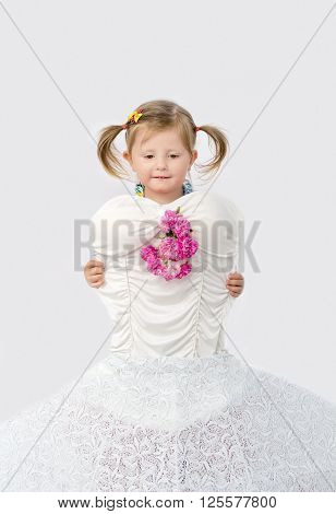 Cute little girl trying on a wedding dress sample on a white background
