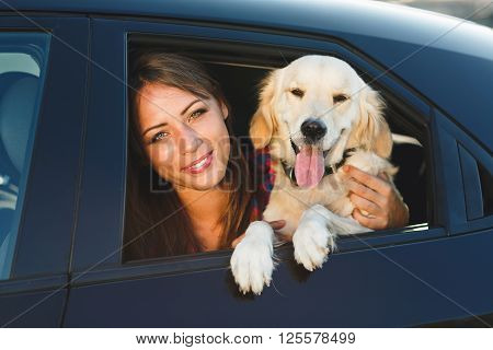 Woman and dog in car on summer travel. Vacation with pet concept.