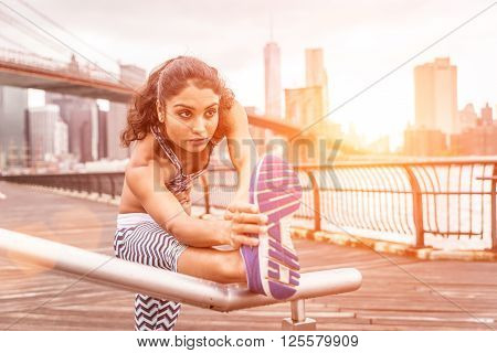 Female runner making stretching before training. New york background