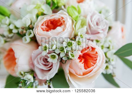 Wedding bouquet. Bride's traditional symbolic accessory. Floral composition with peonies and roses.