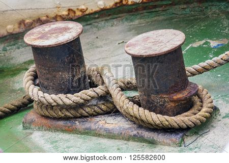Old mooring bollard with heavy ropes closeup.