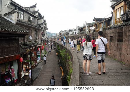 Fenghuang Village China. September 13 2015. Chinese visitors walking on a wall within Fenghuang village (phoenix town) in Hunan province China on an overcast day.
