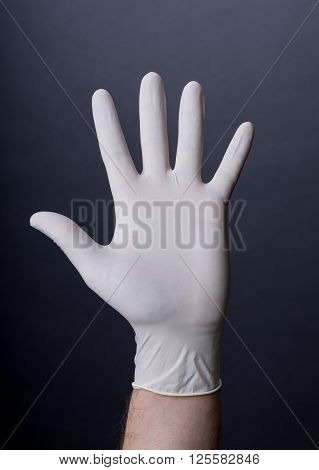 Male palm in latex glove on dark background