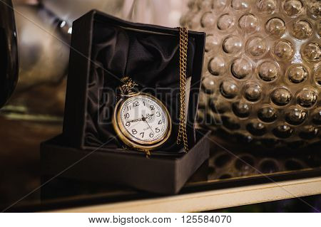 Black box with golden pocket watch on chain
