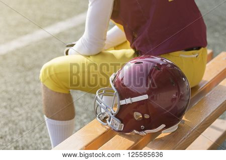 American football player sitting on bench and sports helmet next to him ** Note: Visible grain at 100%, best at smaller sizes