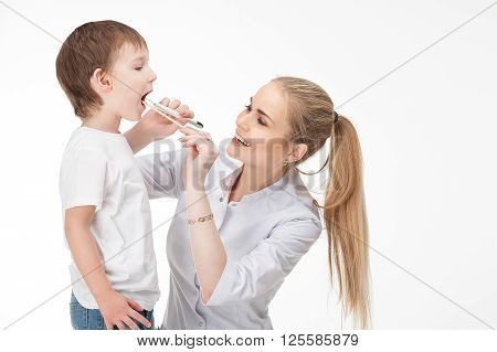 Smiling medical doctor woman with stethoscope. The doctor looks at the baby boy's throat swab and a flashlight Isolated over white background.