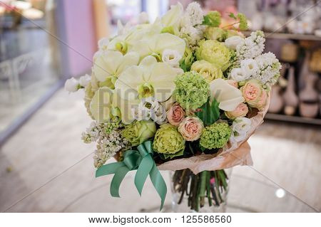 big white bouquet with huge orchids on table ** Note: Visible grain at 100%, best at smaller sizes