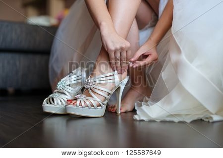 Bride puts on a shoes to a foot standing in a room on a brown floor. Woman buttons white shoe. Mirror surface of the floor. Beautiful wedding white dress.