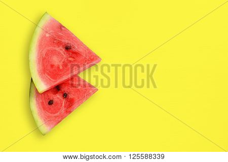 Watermelon slices on yellow table top view