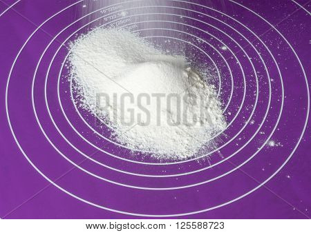 screening wheat flour as background on a purple silicone mat side view