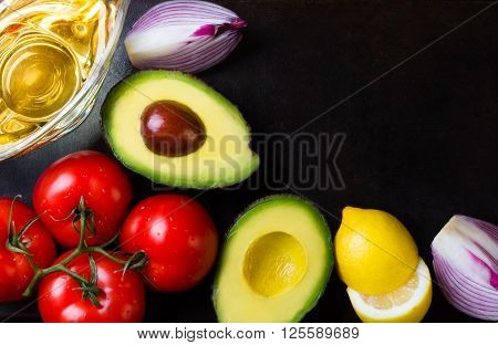 Ingredients for latin american sauce guacamole on black stone background