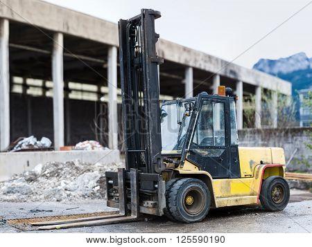 heavy black orange diesel forklift truck at construction site