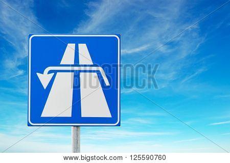 u turn road sign under a cloudy sky