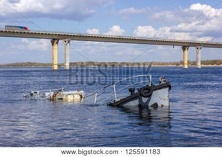 Rusty sunken boat in a blue river