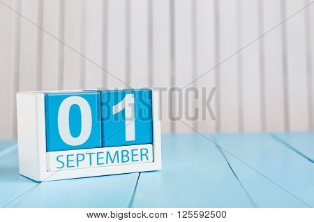 September 1st. Image of september 1 wooden color calendar on blue background. Autumn day. Empty space for text. Back to school time.