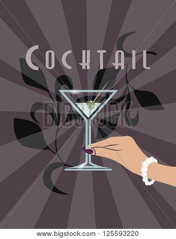 Female hand with necklace holding a Martini cocktail