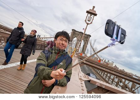 NEW-YORK - CIRCA MARCH 2016: man taking a selfie in New-York. A selfie is a self-portrait photograph, typically taken with a camera phone held in the hand or supported by a selfie stick.