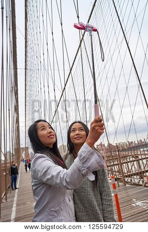 NEW-YORK - CIRCA MARCH 2016: women taking a selfie in New-York. A selfie is a self-portrait photograph, typically taken with a camera phone held in the hand or supported by a selfie stick.