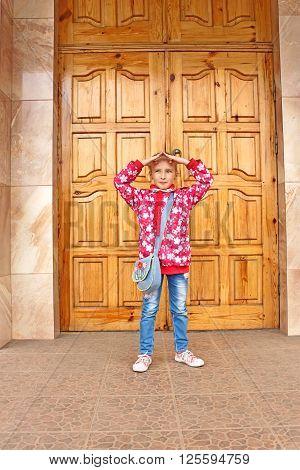 Schoolgirl Posing Before Big Wooden Door