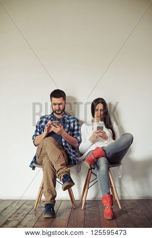 Man and woman are sitting on a chairs and working on their smartphones, background wooden floor and white wall