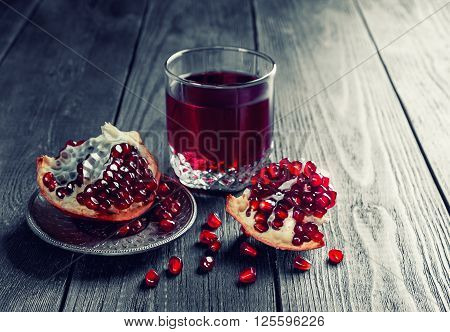 Ripe pomegranate with glass of pomegranate juice on dark wooden table. Toned. Low key. Selective focus.