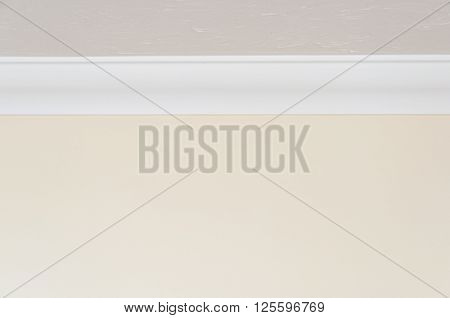Close up of white ceiling moulding and light brown wall for background with copy space at top and bottom
