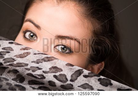 Closeup young brunette model posing with grey brown scarf covering half her face revealing beautiful eyes only, dark background.